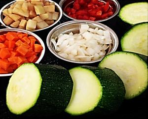 Picar los vegetales y cortar el calabacín en partes iguales.